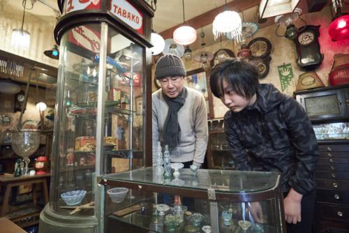 二人が見ているのはニッキ水の瓶。このショーケースは、かつてタバコ屋さんで使われていたもの。入山さんが都内の骨董品店で購入。