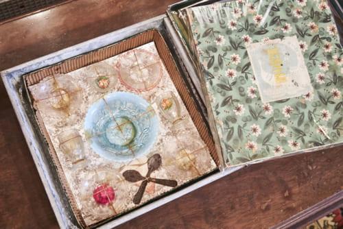 美しいガラス製のままごとセットは、ガラス特有のはかない質感も魅力。当時は緩衝材がないために、麻紐で固定されている。輸出用に作られており、ハイカラなデザインが特徴的。箱のサイズは縦26cm×24cm。