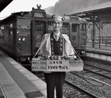観光列車の発着時刻に合わせて人吉駅のホームに姿勢よく立つ。駅弁を満載した木箱の重量はざっと15kg。後ろの列車は特急「かわせみ・やませみ」号、右奥は「いさぶろう・しんぺい」号。