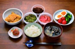 前列中央から時計回りに、ご飯、梅干し、沢たく庵あん、青菜ちりめん、牛の佃煮、辛子明太子 、茹で卵とサラダ(ブロッコリー・プチトマ ト)、味噌汁(蜆)。ご飯は茶碗に1膳、明太子はひと切れ、沢庵は2~3切れが朝の定番だ。牛の佃煮は濃い味付けなので、ほんのひと箸をご飯に混ぜる。