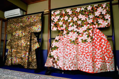 敏明さんの代表作「能衣装 繚乱」(右)は独特の配色と大胆な構図で、満開の桜を画面いっぱいに描いた。「能衣装 花叢(はなむら)」(左)は室町時代の小袖をヒントにしたという豪華な作品だ。