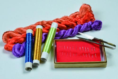 京繍に使う主な道具は絹糸、針、握り鋏。絹糸は8000~1万2000色あり、作品ごとに使い分ける。針は太さ違いで13種類ほどあり、一番細い毛針は人形の睫毛などに使う。