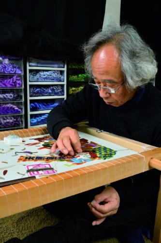 「動物たちの神さん参り」を繍う敏明さん。京繍を始め日本刺繡では、基本的に右手で刺し、左手で引くので両手が使えるように専用の台に布を張る。「時間を忘れて集中できるのは、1日に4時間ぐらいかな」という。