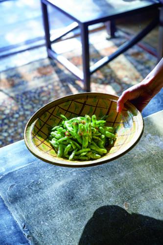 素朴だけれども力強いハンドペイントが施されたアフガンの古鉢は、夏の間、何度もつくる「枝豆のアーリオ・オーリオ」(枝豆をにんにくのみじん切りとオリーブオイルで炒めた料理)にぴったり。黄色の器に緑の枝豆が引き立ちます。