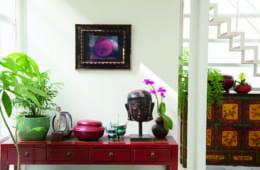 夫が撮影したザクロの写真は、アンティークの額の中でまるで絵のような景色に。中国の漆のコンソールテーブルの上に配した世界の古い小物たち。