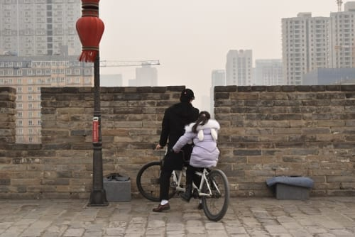 サイクリング合間に城壁から外をのぞく親子