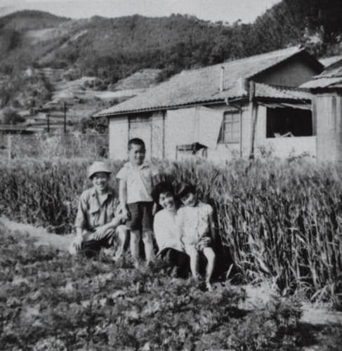 長閑な風景が広がる昭和30年代の広島県呉市の自宅前。立っているのが坂田さん(小学6年生のころ)。右から坂田さんの妹、母。