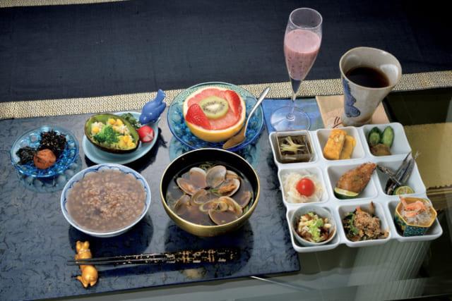 前列中央から時計回りに、味噌汁(浅蜊)、玄米と小あずき豆の五分粥、粥のトッピング(梅干し・岩海苔・梅の実ひじき)、アボカドサラダ(セロリ・シーチキン・コーン・ブロッコリー・ラディッシュ)、果物(グレープフルーツ・キウイフルーツ・苺いちご)、黒米の甘酒、牛蒡茶。白のプレートは手前右から時計回りに、大根おろし(しらす・桜海老)、白和え(ほうれん草・人参・きくらげ・干し椎茸・干し柿・摺ったピーナツと胡桃)、納豆(長芋・長ねぎ)、新玉葱スライス(鰹節・プチトマト)、もずく酢(生姜)、厚焼き卵、漬物(胡瓜の糠漬け・いぶりがっこ)、キビナゴの丸干し(スダチ)、中央は鯖の竜田揚げ(スダチ)。アボカドサラダはマヨネーズとスダチで和え、大根おろしはスダチを絞って食す。白和えの和え衣は豆腐に胡麻、ピーナツ、胡桃を合わせたもの。新玉葱は塩ポン酢でいただく。