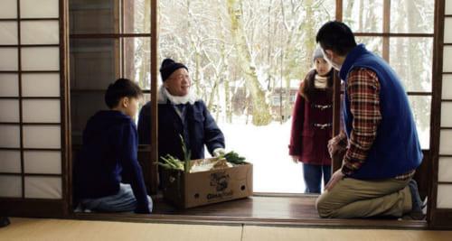 映画『よあけの焚き火』より。作中、狂言方親子が稽古を積む長野県茅野の家を訪れる坂田さん。近所に住む水道屋で、何かと親子の面倒を見るという役柄を演じる。(写真提供/桜映画社)