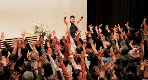 """講演のテーマは幅広い。写真は昨年の「埼玉金融広報委員会」主催の講演。テーマは""""人生を楽しむ秘訣""""で、生島さん自らが手本を示し、参加者全員が健康体操を行なう。"""
