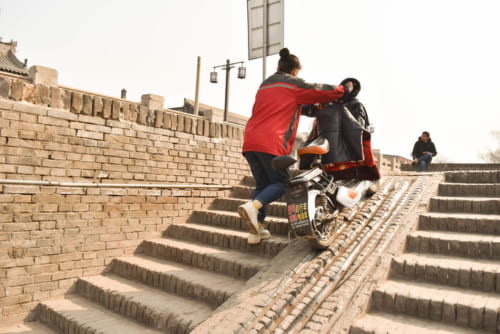 バイクを押して城門から城壁の外へと出る女性
