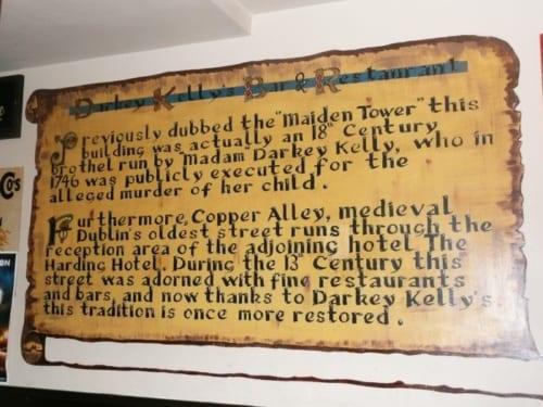 """パブに入るとまず目に入る看板。""""ここは18世紀にMaiden Tower(乙女の塔)』という売春宿だったが、女主人のダーキー・ケリーは自分の子を殺した罪により1,746年に公開処刑された""""と簡単な説明がある。"""