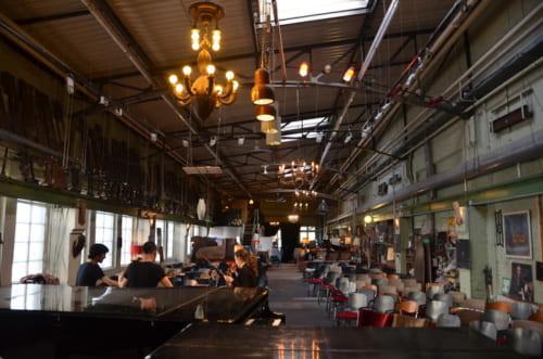 倉庫の中にシャンデリアがぶら下がり、古いピアノや部材が並ぶ。独特の雰囲気だ。