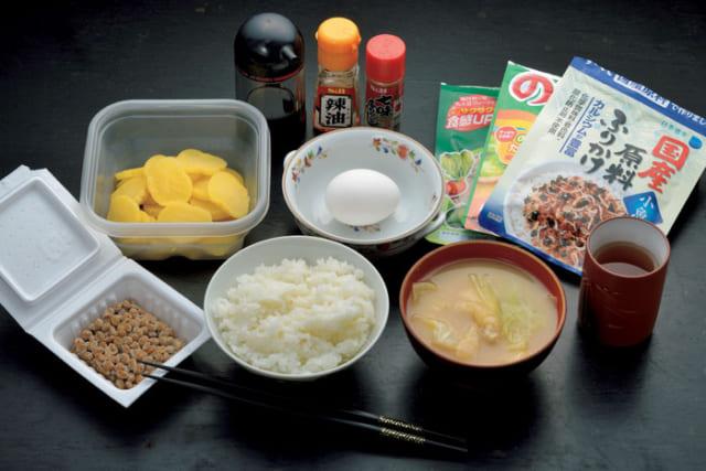 前列中央から時計回りに、ご飯、納豆、沢庵、生卵、ふりかけ(緑黄色野菜・のりたま・小魚の原料ふりかけ)、日本茶、味噌汁(キャベツ・油揚げ)。ふりかけは5~6種類を常備し、そのうち好みの2~3種が食卓に。