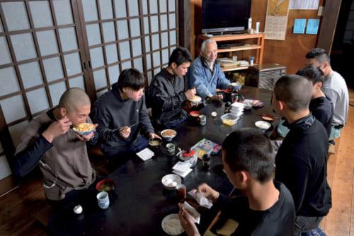 栃木の田所作業所で弟子たちと一緒に朝の食卓に着く小川三夫さん。右列の4人が今年4月に門を敲いた 新人だ。昼食は岩舟作業所の弟子たちも加わり、総勢20人ほどになる。
