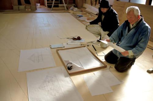 図面を描くのも宮大工の仕事。作業所の2階で、弟子の工藤正雄さんが描いた図面を点検する。多くは語らないが、ひと言がヒントとなる。この図面を基に形板に原寸図を引く。