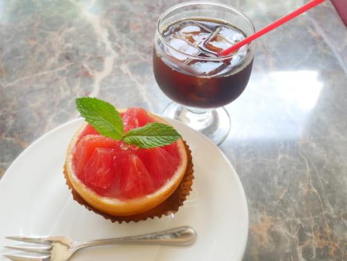 グレープフルーツをくり抜いて、100%果汁でさっぱりと仕上げた生グレープフルーツゼリー(10月頃までの期間限定発売)とアイスコーヒー(ケーキセット950円・税込)。10時間以上かけて抽出した水出しコーヒーは香り高い味わいです。