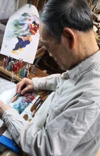 「獅子舞」を爪で織る、平野さん。一日にほんの数センチ程度しか織れないような複雑な文様もあり、大変手間のかかる手法です。だからこそ機械織には出せない目の細かく繊細な表現の織物ができます。