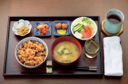 前列左から時計回りに、発芽玄米ご飯(小豆・日本酒)、納豆(大根おろし)、キムチ、梅干し、沢庵、野菜サラダ(キャベツミックス・胡瓜・トマト・貝割れ大根・豆腐)、昆布水、味噌汁(キャベツ・麩・青葱)。お手拭きの上は番茶。発芽玄米ご飯に入れる小豆は、仏さまのお下がりを利用。昆布水は上質の昆布を24時間水に浸けたもので、朝食前に飲む。野菜サラダは市販の胡麻ドレッシングで食す。