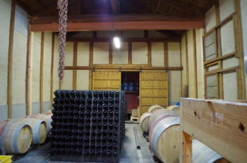 明治時代の蔵をそのまま生かしたカーヴのなかに、熟成用の樽が並ぶ。日本ならではの風情がある。