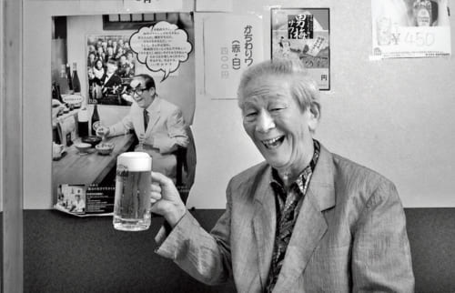 「お酒は好きで何でも飲みますよ」。ここ京王線芦花公園駅に近い居酒屋『ちょうちん』が、小松さんの長年の行きつけの店だ。淀川長治さんの物真似をした自身のポスターと乾杯。