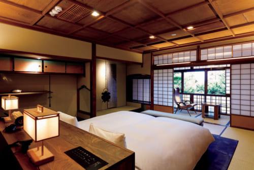 中庭を見下ろす「108 ガーデンビュー スイート」(室料13万円~)の寝室。中塗りの土壁と格ごう天てん井じようが印象的だ。寝具は京都の老舗『イワタ』製。