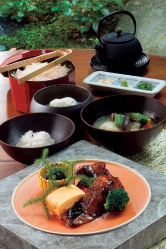 併設レストラン『ラ・ボンバンス 祇園』での和朝食(3500円)の一例。手前は銀鱈の西京焼き、出 汁巻き玉子、茄子田楽など。ほかに具沢山の味噌汁と手作り豆腐。白飯は鰹かつおぶし節と出汁、薬味でお茶漬けも楽しめる。落ち着いた店内には窓が大きく取られ、木々の緑が眩しい。