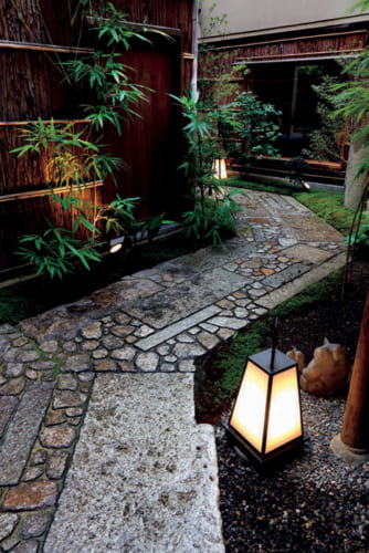 宿の暖簾をくぐると石畳と柴垣が続く小径があり、玄関へと続く。かつての料亭時代の名残を感じる。