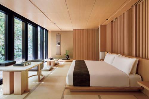 壁一面の窓から苔むした石垣や庭を眺める客室。畳の間にベッドやローテーブルなどが置かれる。家具や照明は特別注文品。