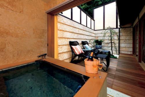 浴室はふたりでゆったり入れる大きな浴槽。チェアや坪庭があり、ソファのあるリビングへと続く。青森ヒバの入浴剤も用意。