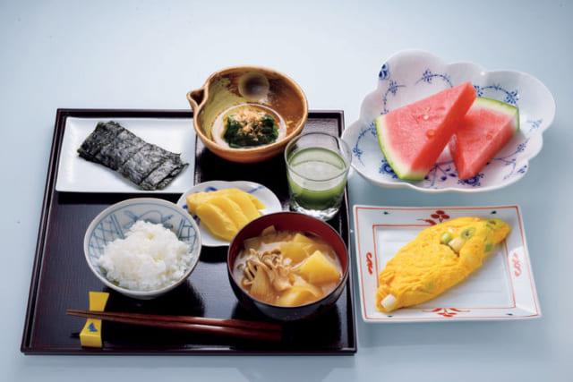 """前列中央から時計回りに、味噌汁(じゃがいも・玉葱・たもぎ茸)、ご飯、焼き海苔、ほうれん草のお浸し(鰹節)、季節の果物(西瓜)、卵焼き(長葱)、中央右は青汁、左は沢庵。米は福井県の""""いちほまれ""""、焼き海苔は広島の『三國屋』製、青汁は『エバーライフ』の""""飲みごたえ野菜青汁""""が定番だ。"""