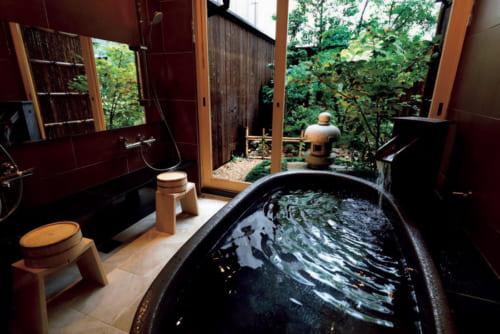 信楽焼の浴槽とふたつのシャワーを備える浴室は自然の趣を残す庭を望む。アメニティはアメリカのシー・オー・ビゲロウのもの。