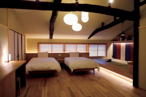 清々しいフローリングと古材の大きな梁が印象的な主寝室。本を読んだり寛いだりできる畳のスペースもある。