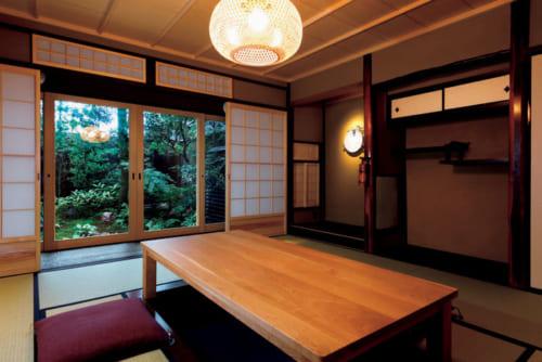 新旧の建具が調和する8畳の和室。掘りごたつ式のカリモク家具の桜材の座卓が置かれる。最大8名で利用できるので3世代旅行にも向く。