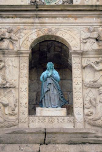 マリア像を牡丹たん菊の文様が囲む。牡丹は中国の、菊は日本の石工が刻んだと伝わる。