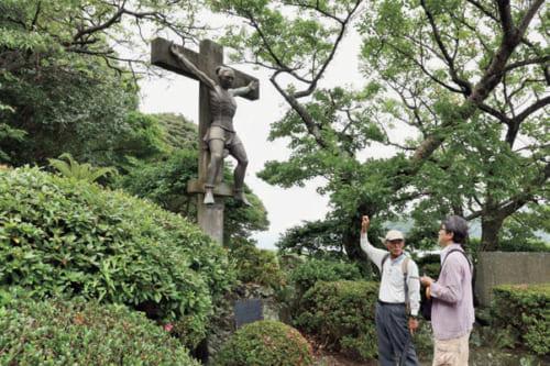 天主堂前庭のヨハネ五島殉教像を前に解説するガイドの山下さん(左)。江戸後期に本土の外そと海め から移住してきたキリシタンの末裔だ。