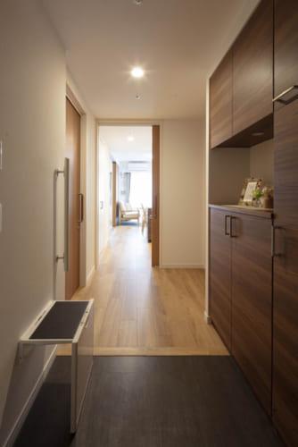段差のない玄関と幅広の廊下。たたき部分に腰掛、手すりを標準装備。