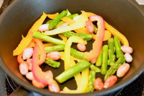 鮭に火が通ったら一度取り出し、落花生、アスパラガス、パプリカを入れやや強火で炒める