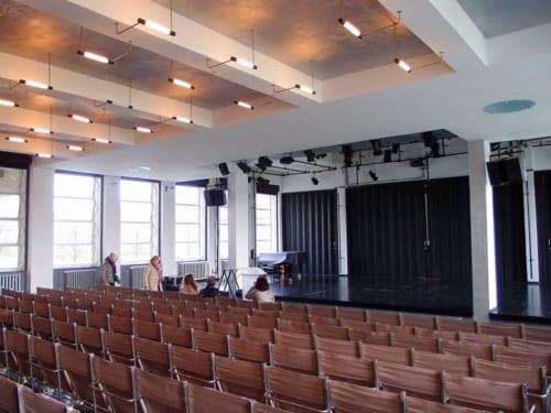 講堂の照明はマックス・クライエブスキ、折りたためるスチールパイプ製の椅子はマルセル・ブロイヤーによるもの。舞台の仕切りを開くと隣の食堂と繋がる仕組み。