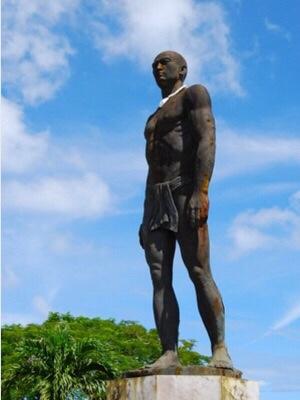 """酋長キプハは1668年6月、サンヴィトレスに彼の支配するハガニアで布教活動を始める権限と教会=現在の聖母マリア大聖堂を建てる土地を与え、グアムで最初に洗礼を受け、古代チャモロ民族を統一に導いた偉大なマガラヒである。1979年に建てられた高さ約3.5メートルの立像は今、グアム博物館に移され、現在パセオ公園入り口に立っているのは2016年4月に新設された2代目。なお、首に下げた白いオオシャコガイのネックレス・シナヒ(Sinahi)はマガラヒなど社会的地位の高い男だけが着用を許された。画像引用:Created by modifying """"Chief Quipuha (Ke puha) Statue"""" by love.jsc is licensed under CC BY 2.0( by is licensed under https://search.creativecommons.org/photos/dfe24570-5846-450d-81b1-0ab3d5796713"""
