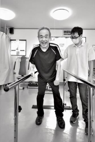 孝さんは毎週火曜、診療所でリハビリに励んでいる。「この平行棒のリハビリが一番キツいんだよ」と孝さん。発病当時に比べたら格段に歩けるようになった。