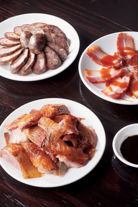 """写真手前は「ダック焼き」1000円。甜麵醤の甘いタレとワインの甘さが一致。右上「釜焼き豚チャーシュー」700円。""""赤い泡""""は豚肉にも向く。左上「自家製羊肉の腸詰」800円。"""