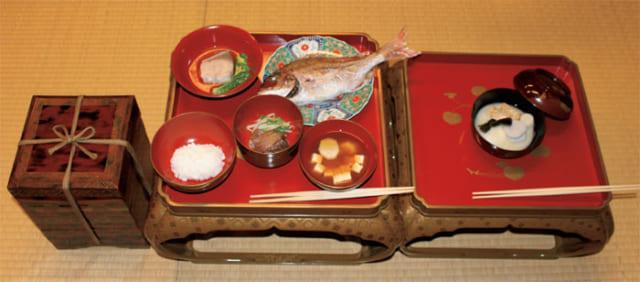 宮本又次『近世なにわ商人の風習と年中行事』より奥村さんが再現した、大坂の豪商・鴻池家の正徳年間の正月料理。右から餅、大根、里芋、焼き豆腐、結び昆布が入った雑煮の膳。一汁三菜の本膳には左上から時計回りに鰤の水煮、小鯛の焼き物、里芋と豆腐の汁、鰹と大根とセリの膾(酢の物)、飯。四季蒔絵重引には酒肴が入る。