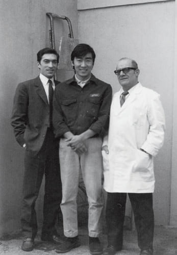 イタリア、ミラノのアルフレックスの工場で工場長ブッツィオさん(右)と設計部門部長のプリンチピさん(左)に挟まれた保科さん。ふたりの師匠から家具づくりを仕込まれた。