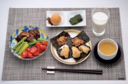 前列中央から時計回りに、玄米餅の海苔巻き、納豆の海苔巻き(炒り白胡麻)、野菜サラダ(プチトマト・グリーンアスパラガス・茹で椎茸・スナップエンドウ)、デザート(胡麻団子・本葛の冷菓)、低脂肪牛乳、菊いも茶。玄米餅は角餅1枚を3等分にして焼く。野菜サラダには、市販の油分をカットしたグリーンドレッシングか胡麻ドレッシングをかける。デザートは2品ともに『南国酒家』の特製だ