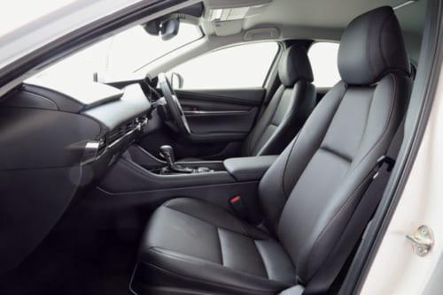 ヘッドレストと背もたれが一体となった座席。左右の脇腹もしっかりと支える。座席の表皮は、黒色の本革、布のほかに白色の本革も選べる。