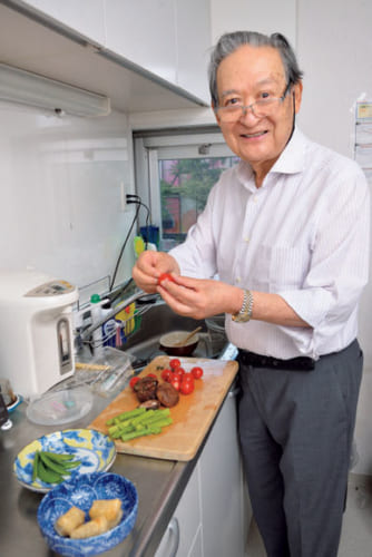 「野菜サラダには一年中、トマトを欠かしません。このプチトマトはヘタを取るだけなので重宝。ドレッシングがのりやすいように、半分に切ります」と、事務所の台所に立つ。