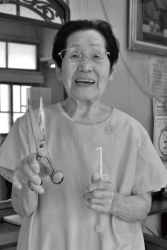 """大正5年、栃木県生まれ。理容師歴80年以上で、現在も現役で仕事をしている女性理容師。昭和7年、16歳で理容師修業のため上京。同11年、理容師免許を得る美容術試験に合格。同14年に同業の箱石二郎と結婚し、夫婦で新宿の落合に理容室を開業。盛業だったが夫は出征。終戦後の昭和28年、その戦死公報を受けて郷里の現・那珂川町で『箱石理容室』を開店。その腕の確かさから""""東下りの理容師""""と評判をとり、今日に至る。"""