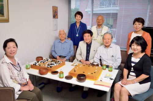 """宮田さんが主宰する囲碁サロン""""木曜会""""の仲間と一緒に。中央左からふたり目が講士の西實さん、その右が宮田さん。性別、年齢、段位を問わず、囲碁好きの10人ほどが集まる。"""