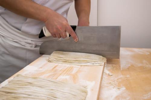 手で揉み込んだそば粉を面状にして麺にしていく蕎麦切り。修行した職人の技術が冴える。